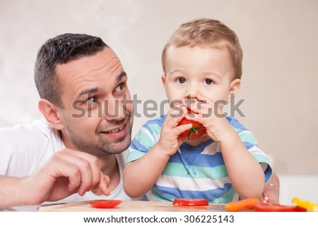 Cheerful little child is sitting at the table and eating tomato with appetite. His parent is kneeing near him. The man is looking at his son with joy and smiling - stock photo