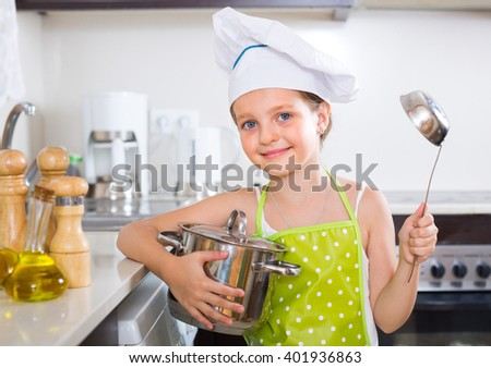 Cheerful  little girl cooking alone at home kitchen