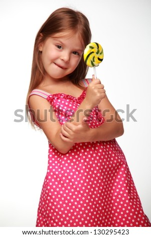 Cheerful little girl eating a large yellow lollipop - stock photo