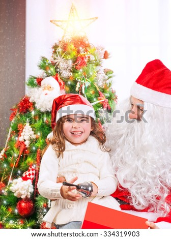 Cheerful little girl enjoying presents receiving from Santa Claus, spending happy winter holidays near Christmas tree at home - stock photo
