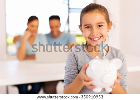 cheerful little girl holding piggybank with parents on background - stock photo