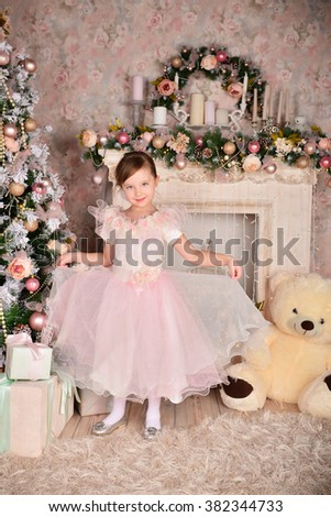Cheerful little girl in a New Year's dress, posing on a background of the Christmas tree - stock photo