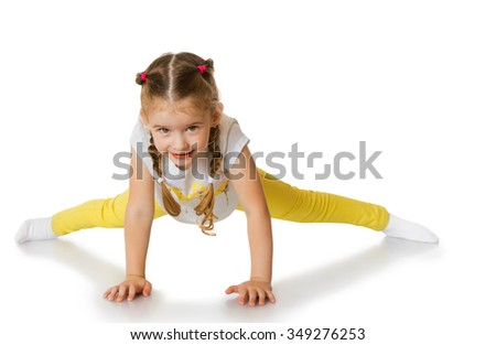 Cheerful little girl in a yellow tracksuit is trying to do the splits - Isolated on white background - stock photo