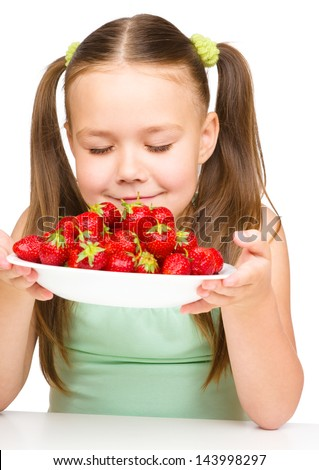 Cheerful little girl is smelling strawberries, isolated over white - stock photo