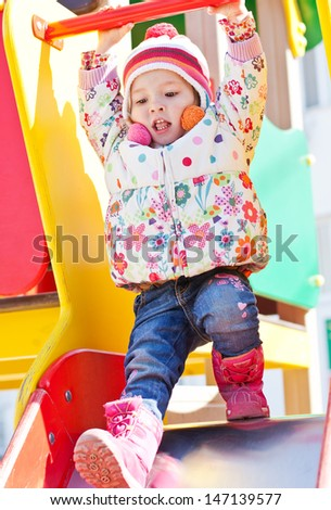 cheerful little girl playing on the playground on a sunny day - stock photo