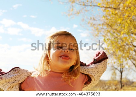 Cheerful little girl  puts out the tongue in park.  - stock photo