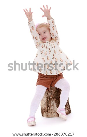 Cheerful little girl raised his arms sitting on a birch stump-Isolated on white background - stock photo