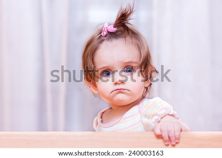 cheerful little girl sits in the crib at home - stock photo