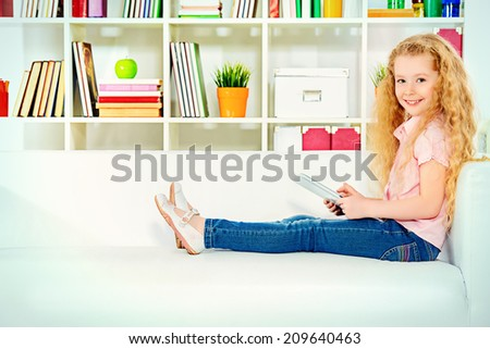 Cheerful little girl sitting on a sofa at home and holds a digital tablet. - stock photo