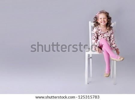 Cheerful little girl sitting on the chair with smile, a lot of copy space - stock photo