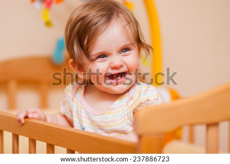 cheerful little girl standing in the crib at home - stock photo
