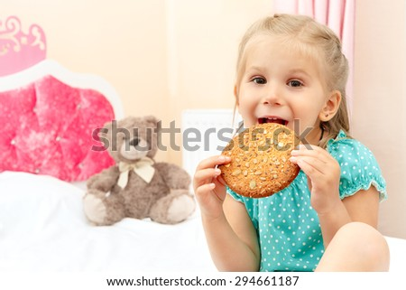 Cheerful little girl with chocolate chip cookies - stock photo