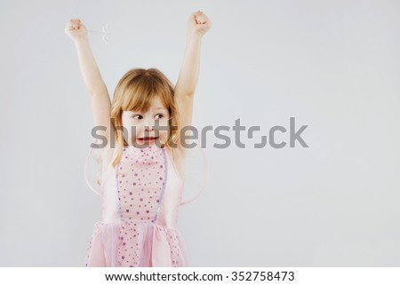Cheerful little girl, with curly blond hair, wearing on pink dress and fairy wings, puts her hands up with magic stick, on white background, in studio, waist up - stock photo