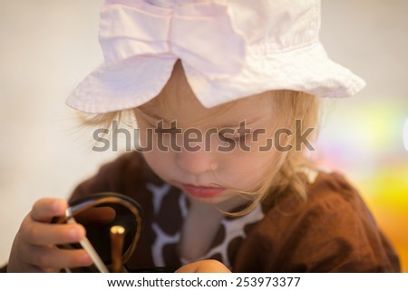 cheerful little girl with Down syndrome with glasses resting on the sea coast - stock photo