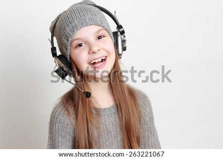 Cheerful little girl with headphone singing - stock photo