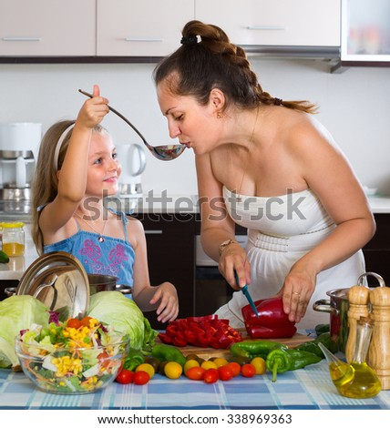 Cheerful little girl with mom cutting vegetables for soup at home kitchen - stock photo