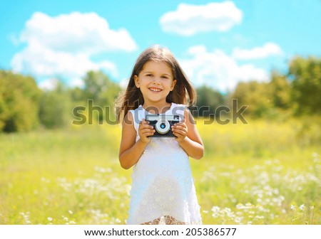 Cheerful little girl with old retro vintage camera in summer sunny day - stock photo