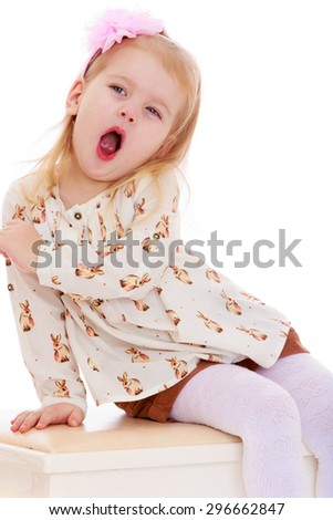 Cheerful little girl with short blond hair who is holding a pink headband in a bright silk shirt and brown shorts ,sits on a white wooden bench and his mouth wide open yawning- isolated on white - stock photo
