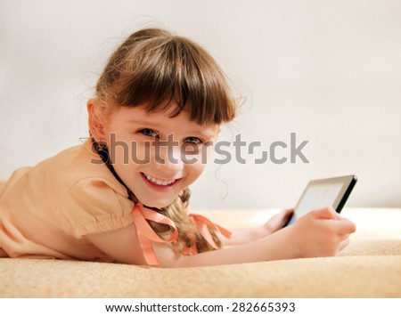 Cheerful Little Girl with Tablet Computer on the Sofa - stock photo