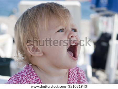 Cheerful little girl with wide open mouth. European amazing blond child with perfect blue eyes. Having fun in summer at the beach. Closeup portrait of charming healthy child.  Colorful photo - stock photo