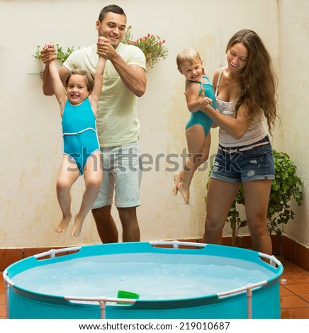Cheerful little girls and parents having fun in pool at terrace. Focus on man  - stock photo