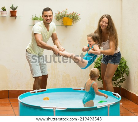 Cheerful little girls with happy young parents having fun in pool at terrace. Focus on man  - stock photo