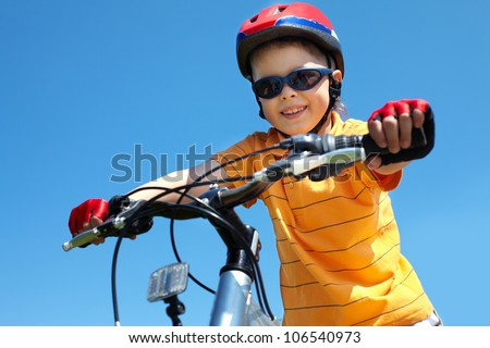 Cheerful little guy in protective sportswear riding a bike - stock photo