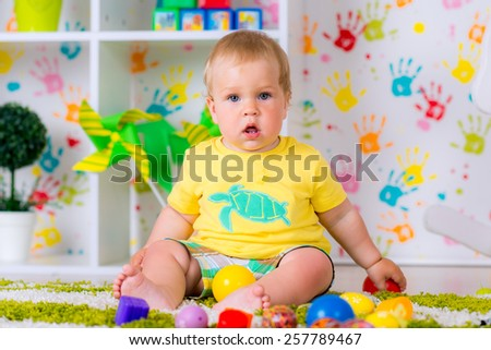 cheerful little kid playing with toys in the nursery, fun game very happy - stock photo