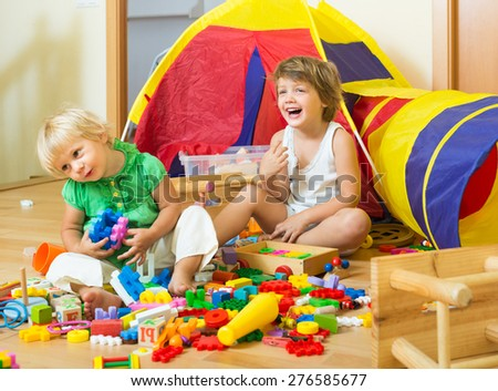 Cheerful little siblings playing with toys together in home interior - stock photo