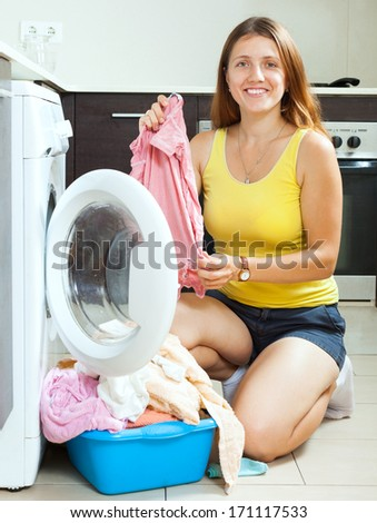Cheerful long-haired girl doing laundry  at home - stock photo