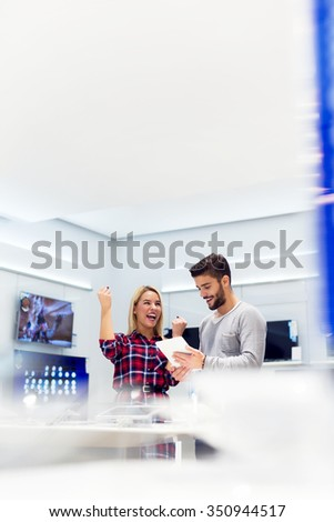 Cheerful lovely couple is at store and they are looking for a new tablet. She is very happy and she is holding her fist up. Shallow depth of field. - stock photo