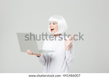 Cheerful lovely young woman standing and using laptop - stock photo