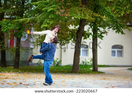 Cheerful loving couple having fun together on a fall day - stock photo