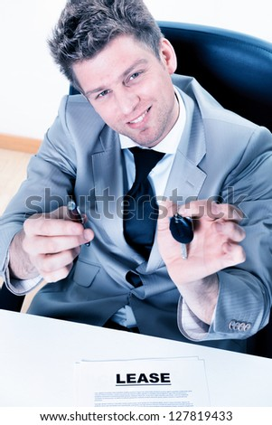 cheerful male agent proposes to sign a lease with handing over the keys - stock photo
