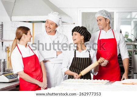 Cheerful male and female chefs conversing while preparing pasta in commercial kitchen - stock photo