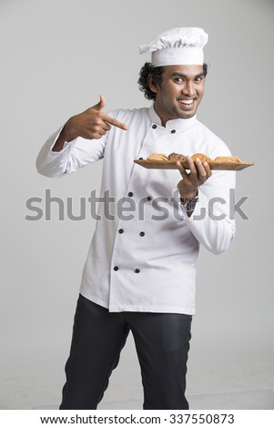 Cheerful male chef posing with cookies isolated over grey gradient background - stock photo
