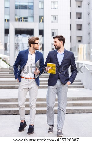 Cheerful male colleagues are communicating with joy - stock photo