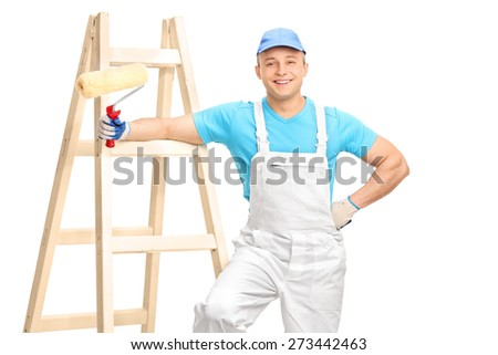 Cheerful male decorator in a white jumpsuit and a blue shirt holding a paint roller and leaning on a wooden ladder isolated on white background - stock photo