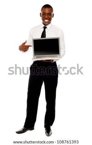Cheerful male executive pointing at open laptop, full length portrait - stock photo