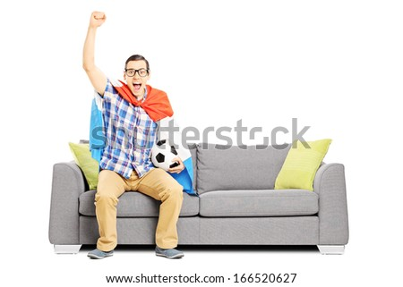 Cheerful male sport fan with football and flag watching sport isolated on white background - stock photo