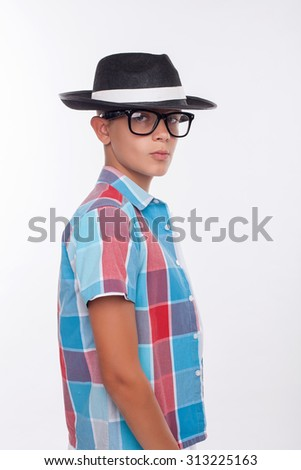 Cheerful male teenager is standing in cool black hat and eyeglasses. He is looking forward with seriousness. Isolated on background - stock photo