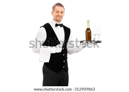 Cheerful male waiter with a bow-tie and black vest holding a tray with a champagne and two empty glasses on it isolated on white background - stock photo