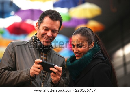 Cheerful man and woman friends looking at mobile smart phone - stock photo