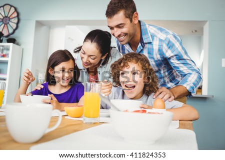 Cheerful man and woman with children during breakfast at home - stock photo
