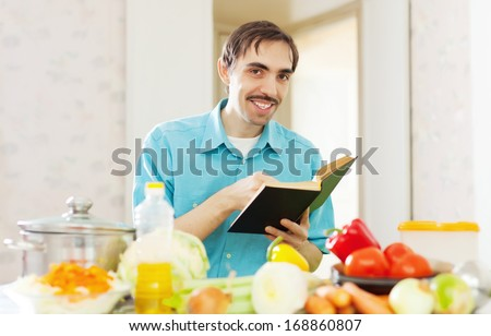 cheerful man cooking  vegetables with cookbook at kitchen - stock photo