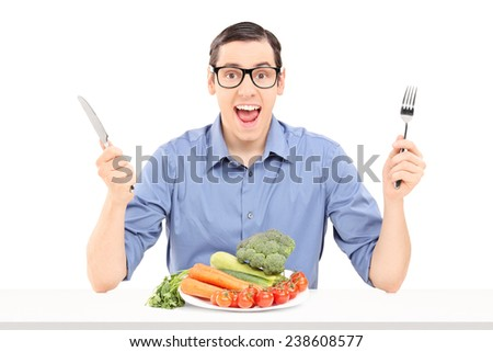 Cheerful man eating a bunch of vegetables isolated on white background - stock photo
