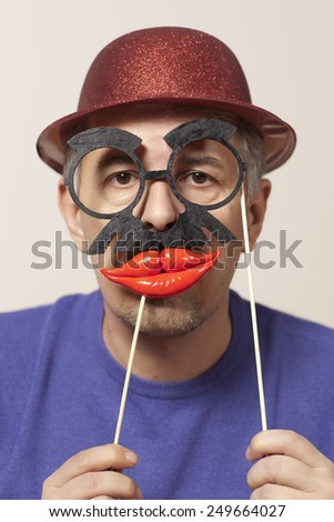 Cheerful man in a mask and a red hat - stock photo
