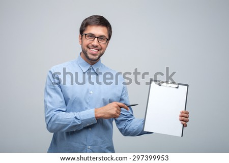 Cheerful man is showing a folder with papers to camera. He is pointing at it with the pen and smiling. Isolated on grey background - stock photo