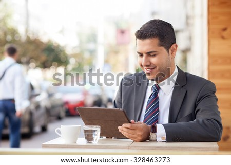 Cheerful man is sitting and holding laptop in cafe outdoors. He is looking at technology and reading with interest. The worker is drinking coffee and smiling. Copy space in left side - stock photo