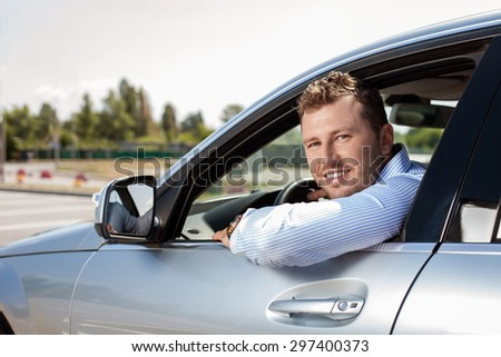 Cheerful man is sitting at steering wheel near airport. He is looking through window and smiling - stock photo